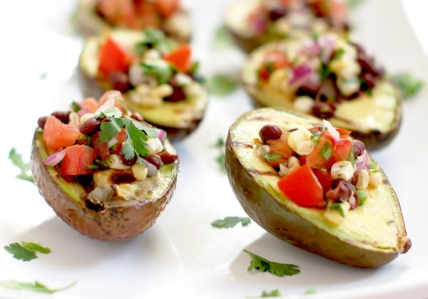 Grilled avocados are stuffed with a light and fresh mixture of corn, black beans, and tomatoes in this elegant yet simple appetizer, side dish, or entrée. Get the gluten-free and vegan recipe @jlevinsonrd.