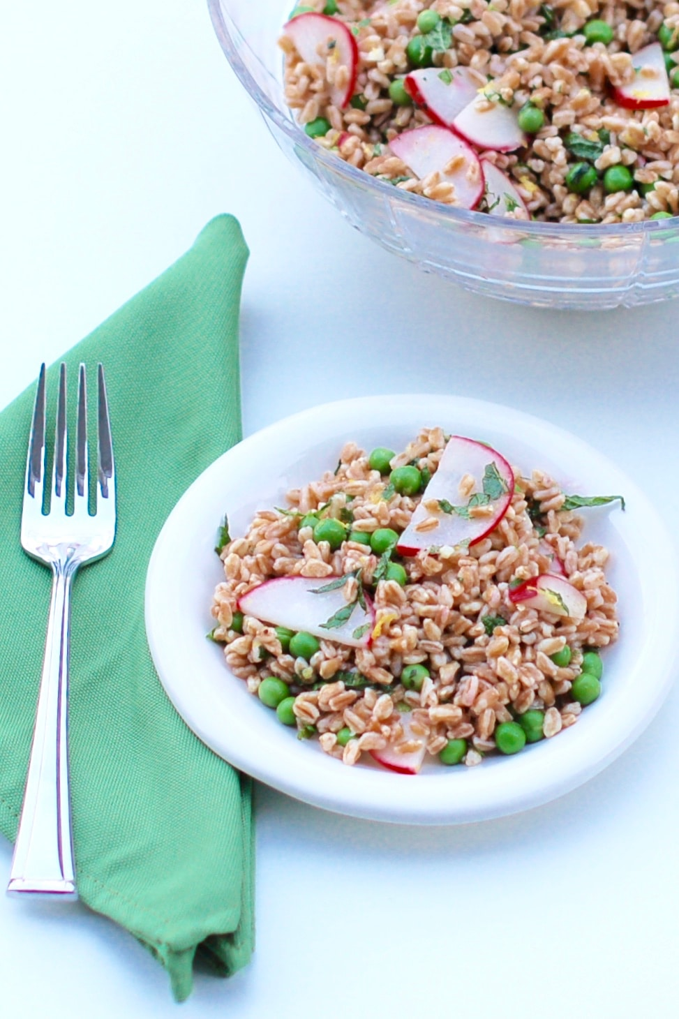 Nutty farro, crunchy radishes, and sweet peas are tossed together in a tart lemon mint dressing in this bright Spring Pea and Radish Farro Salad! #vegan #nutfree #springrecipes #farro #wholegrains