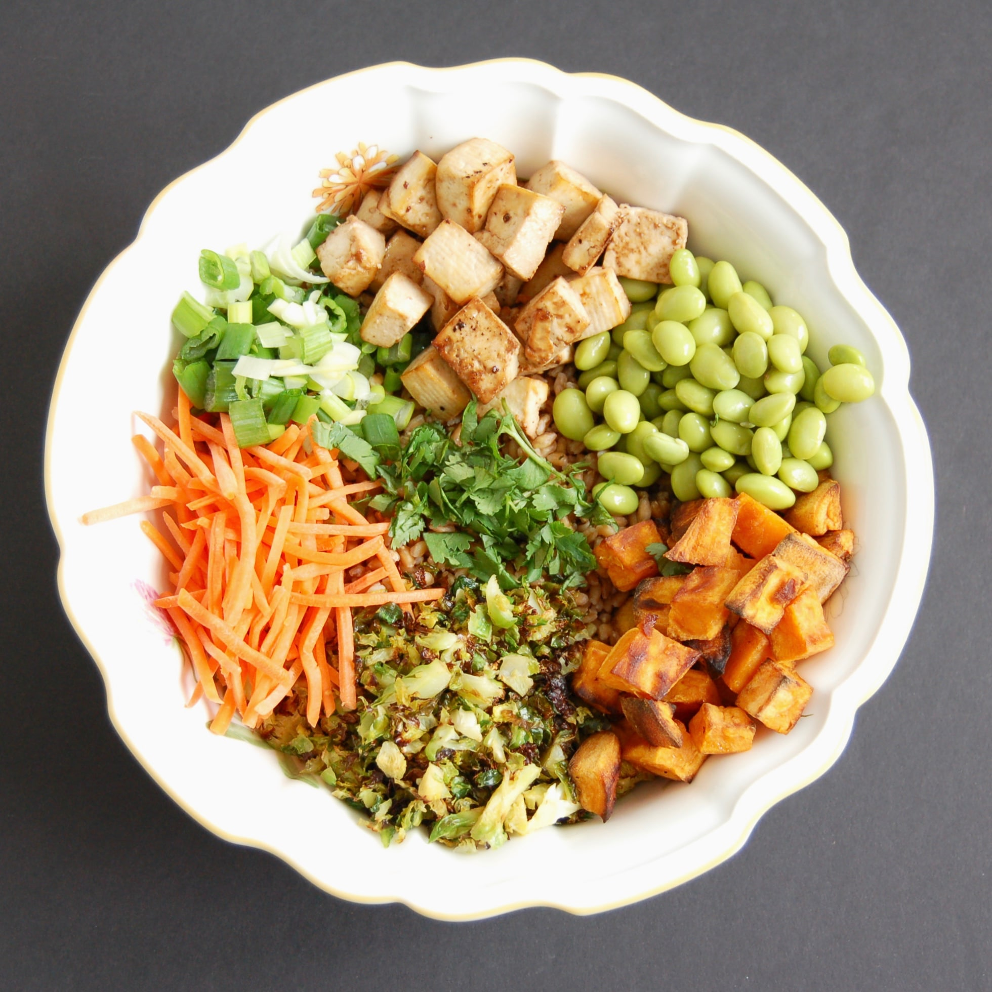 Asian-Style Farro Buddha Bowl with Crispy Baked Tofu | Whole grain farro is topped with shredded carrots, edamame, roasted Brussels sprouts and sweet potatoes, and crispy baked tofu and then tossed with a miso sesame dressing for a vegetarian and vegan-friendly meal the whole family will love. Get the vegetarian, egg-free, and dairy-free recipe @jlevinsonrd.