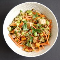 Asian-Style Farro Buddha Bowl with Crispy Baked Tofu | Whole grain farro is toppedwith shredded carrots, edamame, roasted Brussels sprouts and sweet potatoes, and crispy baked tofu and then tossed with a miso sesame dressing for a vegetarian and vegan-friendly meal the whole family will love. Get the vegetarian, egg-free, and dairy-free recipe @jlevinsonrd.