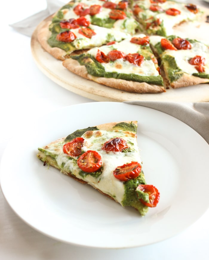 Rosemary-Roasted Tomato Pesto Pizza | Whole wheat crust is topped with a nut-free kale pesto lightened up with ricotta cheese, rosemary-roasted tomatoes, and fresh mozzarella cheese. A delicious and healthier way to enjoy pizza night at home. Get the vegetarian and nut-free recipe @jlevinsonrd.
