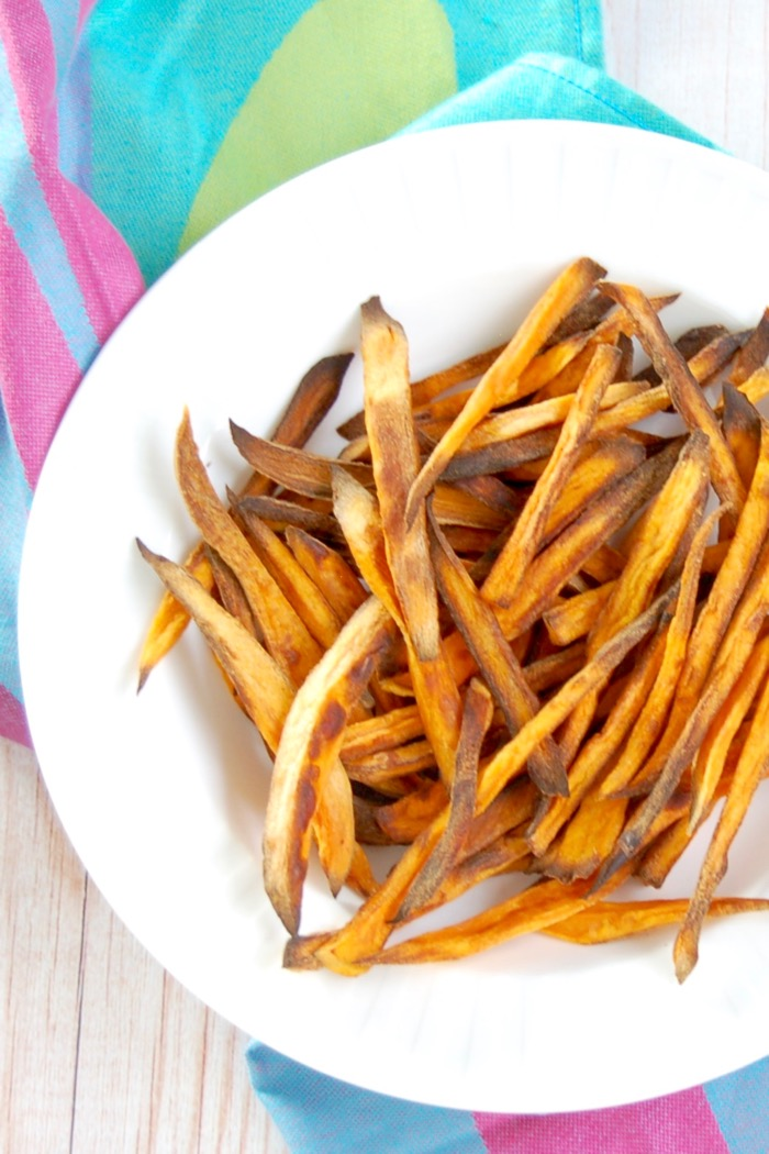 Crispy baked sweet potato fries are easy to make, kid-friendly, and delicious. The perfect side dish for any weeknight family dinner! Get the gluten-free and vegan recipe @jlevinsonrd.