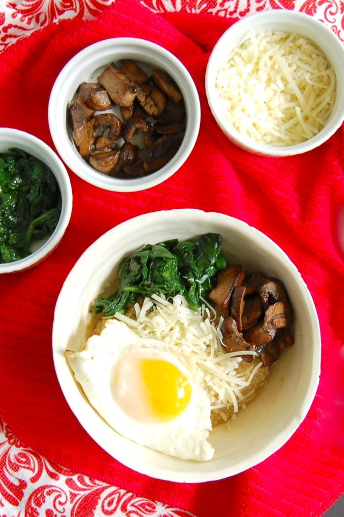 Get a serving of vegetables and protein at breakfast with this umami-rich savory oatmeal breakfast bowl with spinach, mushrooms, and fried egg. Get the gluten-free, vegetarian, and vegan-friendly recipe @jlevinsonrd.