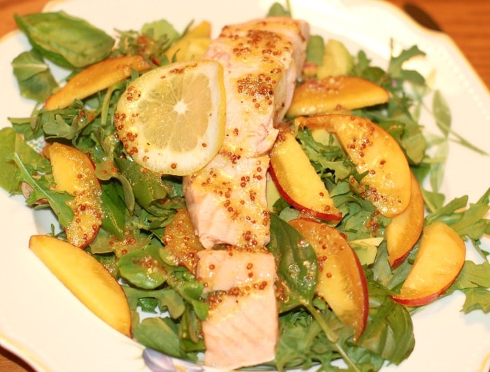 poached salmon and peaches on top of a bed of arugula