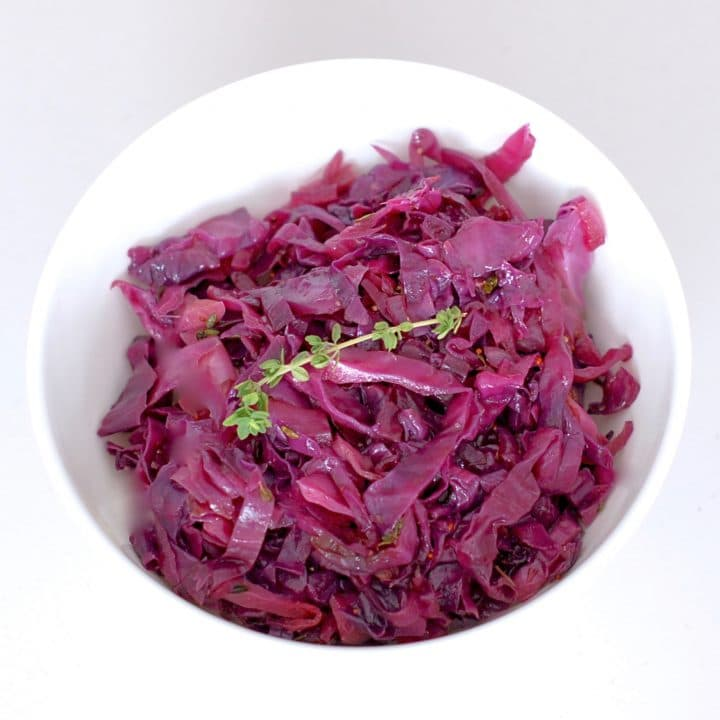 Braised Red Cabbage and Apples with Maple & Thyme is a pretty and delicious side dish to add to your plate. Red cabbage and apples are braised with maple syrup, cider vinegar, mustard, and thyme for a sweet and savory combination that highlights some of the most popular flavors of the fall and winter season. #Vegan #GlutenFree
