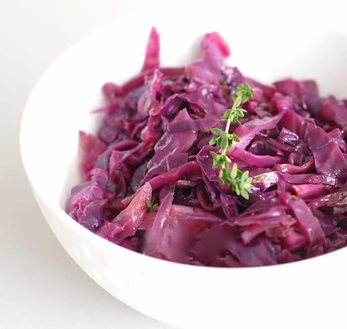 close up side view of braised red cabbage and apples