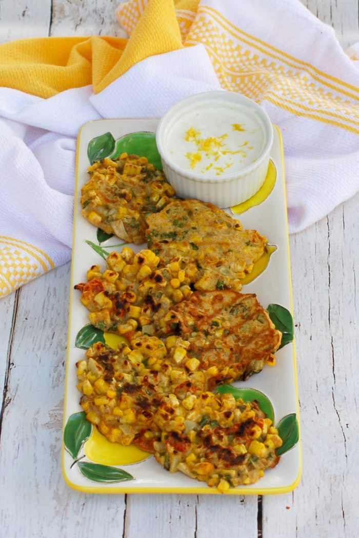 overhead picture of Corn & Basil Cakes on serving plate with ramekin of yogurt sauce