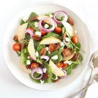 Spinach Pear Salad with Goat Cheese and Lemon Thyme Vinaigrette | There's nothing boring about this flavor-packed salad! A bed of baby spinach is topped with crisp pears, juicy tomatoes, crunchy red onions and pecans, and creamy goat cheese, and tossed in a bright and aromatic lemon thyme vinaigrette. Recipe via jessicalevinson.com | #glutenfree #vegetarian #salad #goatcheese #pears