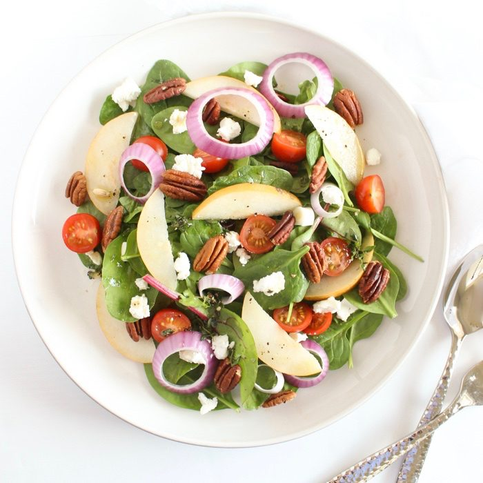 Spinach Pear Salad with Goat Cheese and Lemon Thyme Vinaigrette | There's nothing boring about this flavor-packed salad! A bed of baby spinach is topped with crisp pears, juicy tomatoes, crunchy red onions and pecans, and creamy goat cheese, and tossed in a bright and aromatic lemon thyme vinaigrette. Get the gluten-free, vegetarian recipe @jlevinsonrd.