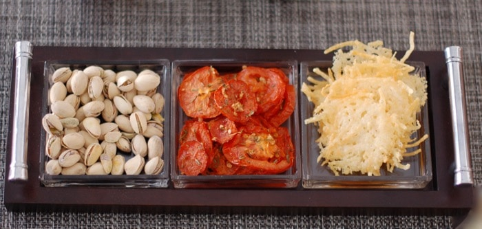 snack platter with pistachios, roasted tomatoes, and cheese crisps