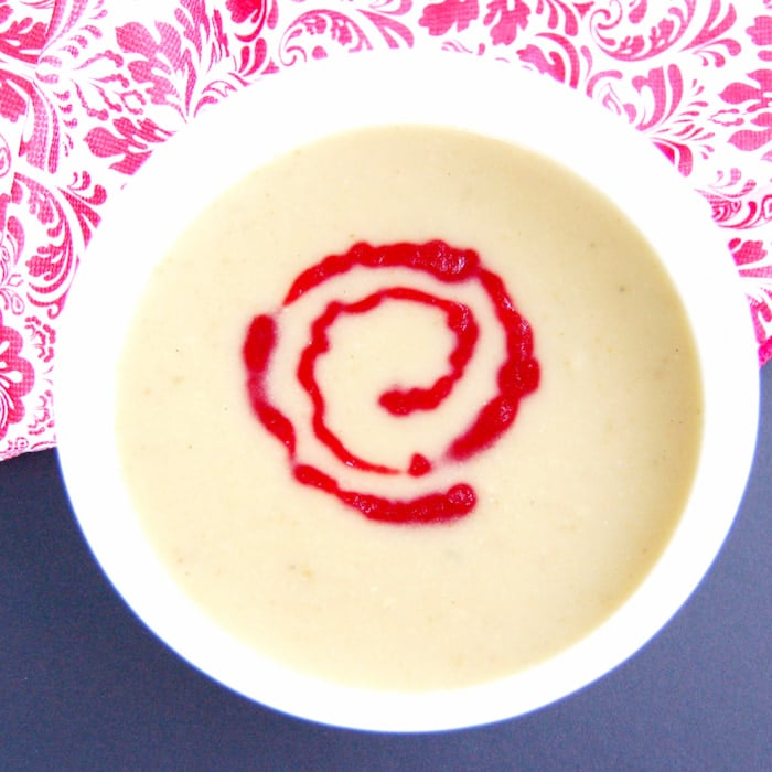 bowl of parsnip pear soup with cranberry coulis
