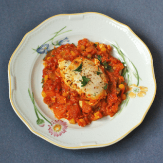 Summer Shakshuka | This summery twist on the classic Israeli breakfast recipe is an easy one-skillet dish of sautéed bell peppers, summer squash, corn, onions, and garlic in a Mediterranean-spiced tomato sauce with poached eggs and feta cheese. Get the gluten-free, vegetarian recipe @jlevinsonrd.