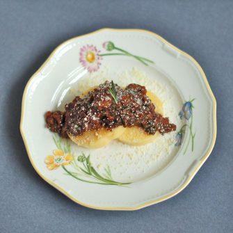 Umami-rich, vegetarian lentil bolognese served over polenta cakes or your favorite pasta is a filling and flavorful dinner meal.
