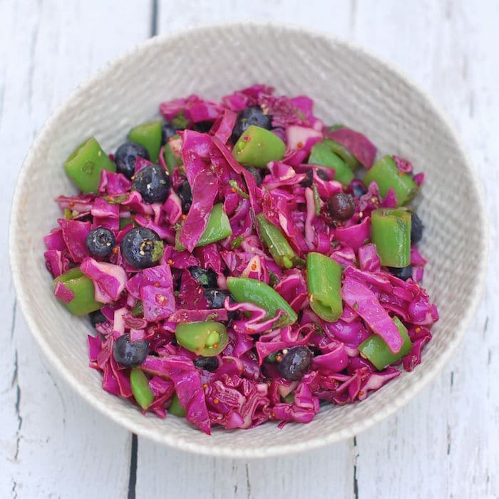 This colorful red cabbage blueberry salad is quick and easy to make, pretty to look at, and filled with health-enhancing nutrients. Enjoy it at your next summer social gathering! Recipe via JessicaLevinson.com | #cabbage #blueberries #slaw #salad #glutenfree #dairyfree #vegan #vegetarian
