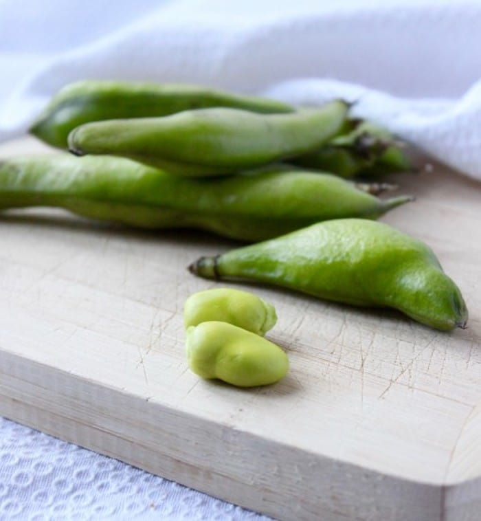 Fresh Fava Beans in pods on cutting board