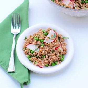 Pea and Radish Farro Salad on white plate with fork on green napkin