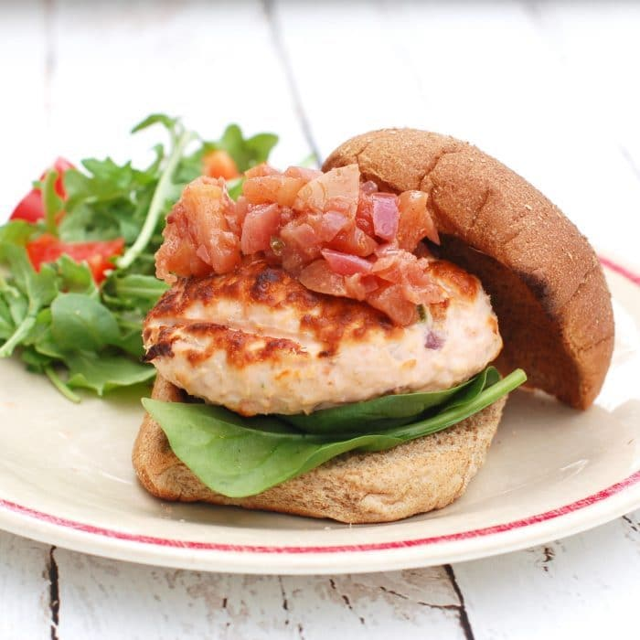 Grilled Fresh Salmon Burgers on whole wheat bun with apple chutney on plate