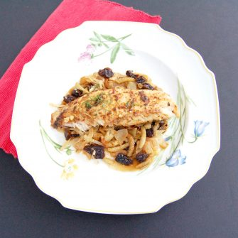Baked Tilapia with Fennel & Dried Plums | Herb and spice-rubbed baked tilapia is served over a bed of caramelized fennel, onions, and dried plums for a quick and easy weeknight dinner and delicious way to boost your seafood intake. Get the gluten-free and dairy-free recipe @jlevinsonrd.