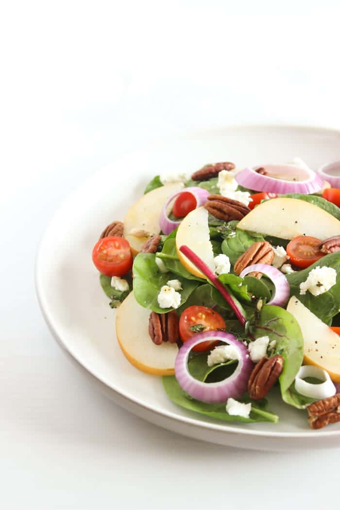 Spinach Pear Salad with Goat Cheese on White Plate