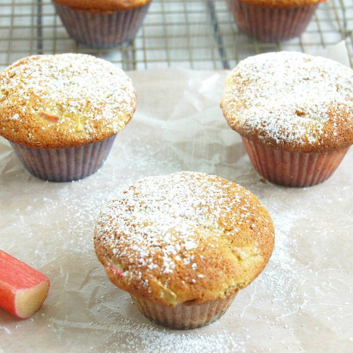 Rhubarb Ginger Lemon Muffins on parchment paper with Powdered Sugar
