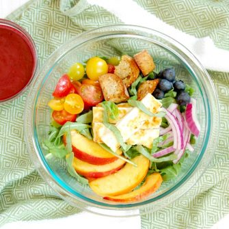 bowl of peach panzanella salad tossed with blueberry balsamic dressing