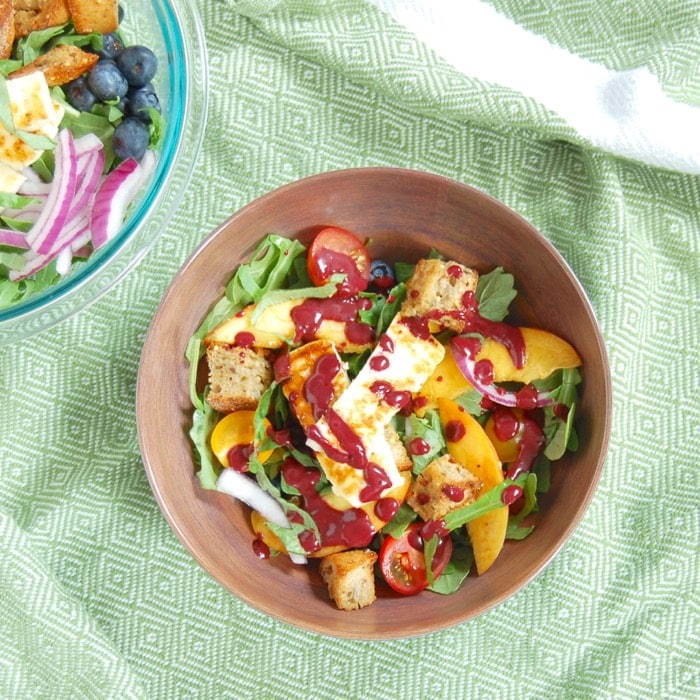 bowl of peach panzanella salad tossed with blueberry balsamic salad dressing