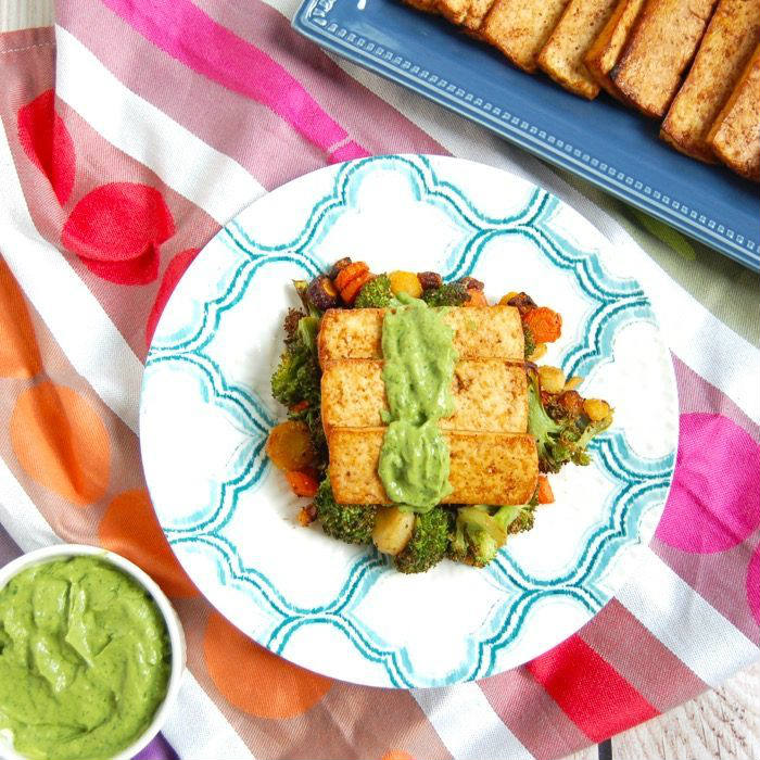 Grilled Tofu topped with with creamy Cilantro Avocado Sauce over a bed of roasted veggies