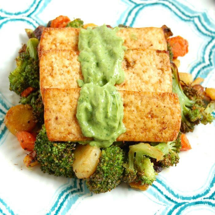 Close Up of broiled tofu over roasted broccoli, carrots, and parsnips topped with avocado sauce
