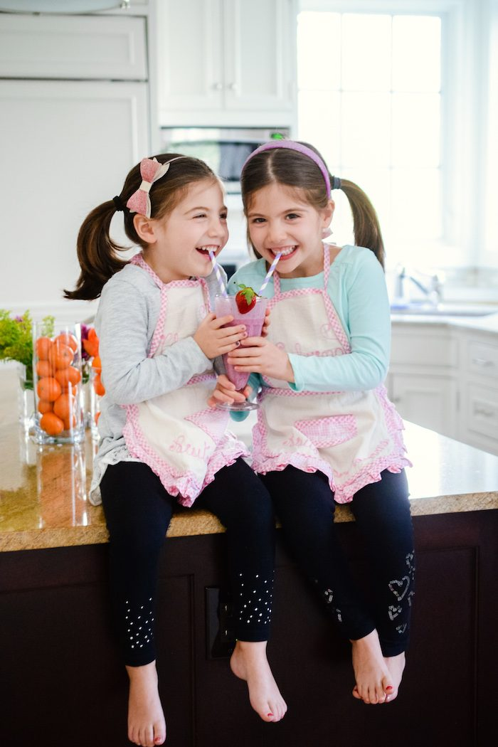 Twin five year old girls drinking a strawberry smoothie.