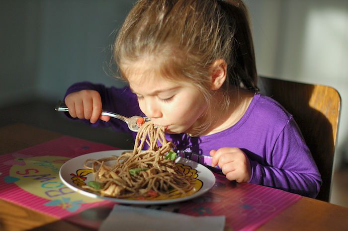 My daughter at 3 years old eating peanut soba noodles with vegetables.