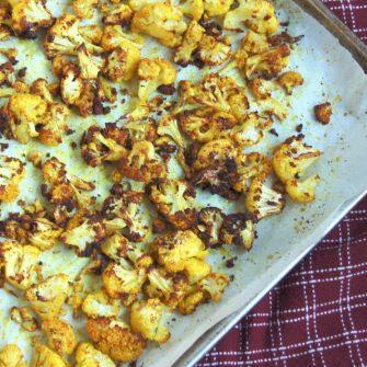 close up of roasted turmeric cauliflower on baking sheet