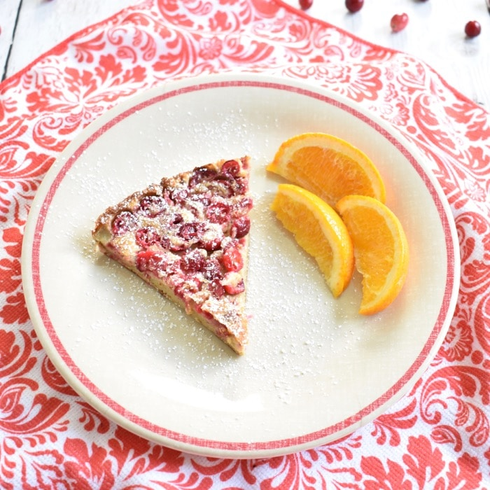 slice of cranberry dutch baby on plate with sliced oranges