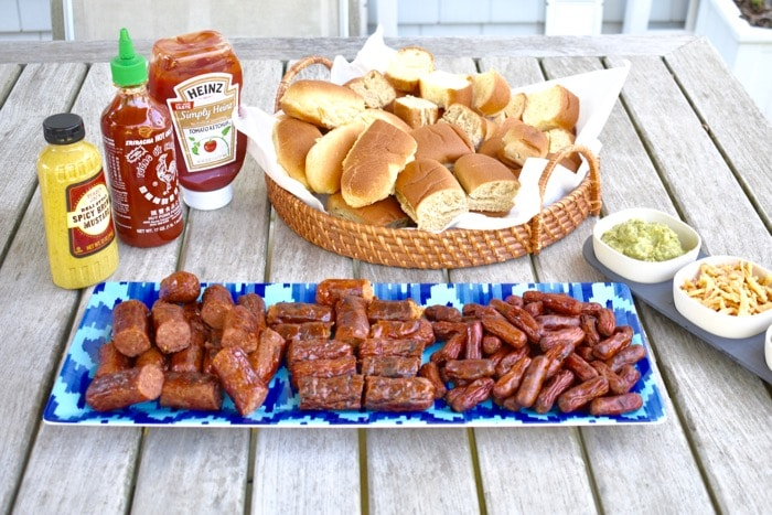 hot dog and sausage slider bar with all the fixings on picnic table