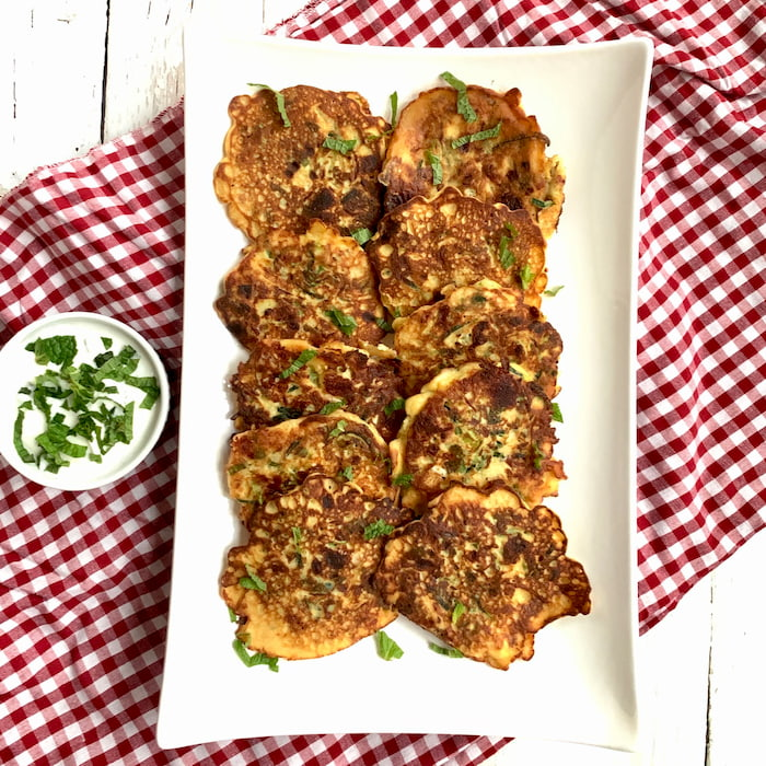 zucchini pancakes on white serving platter with side ramekin of yogurt sauce