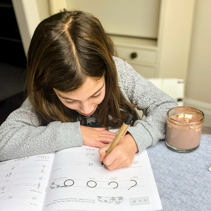 young girl doing homework with a cup of hot chocolate
