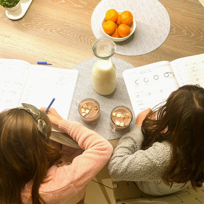 overhead image of children doing homework with hot chocolate